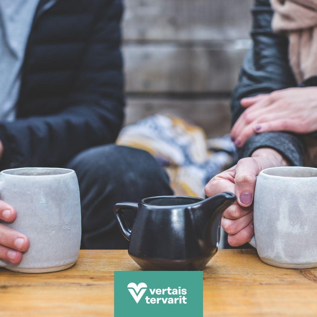 Kuvassa on lähikuva kahdesta henkilöstä istumassa vierekkäin. Henkilöistä näkyy vain kädet. TOinen henkilö pitää kädessään kahvikuppia. Toisen henkilön kahvikuppi on kuvan etualalla pöydällä.