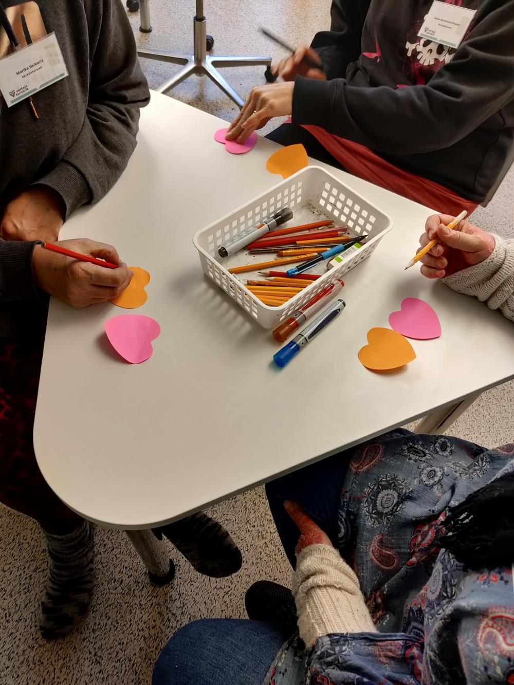 Kolme ihmistä kirjoittaa post-it lapuille kynällä pöydän ääressä.