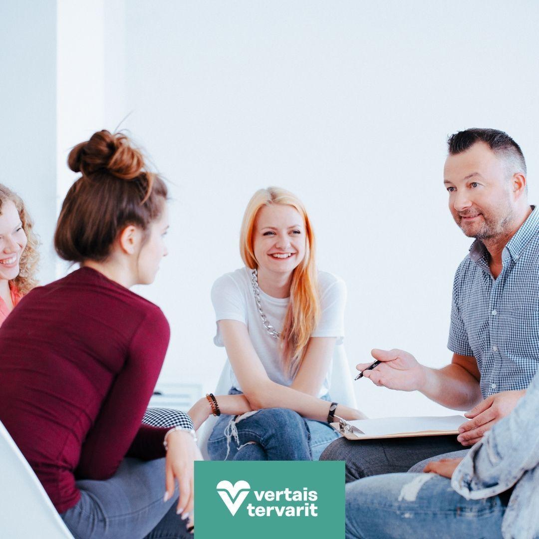 Kuvassa on ryhmäihmisiä istumassa penkillä. Penkit on asetattu ympyrän muotoon ja ihmiset juttelevat toisilleen.