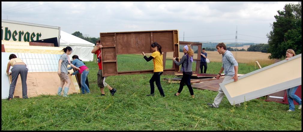 Kuvassa joukko vapaaehtoisia kantaa puukehikoita nurmikentällä.