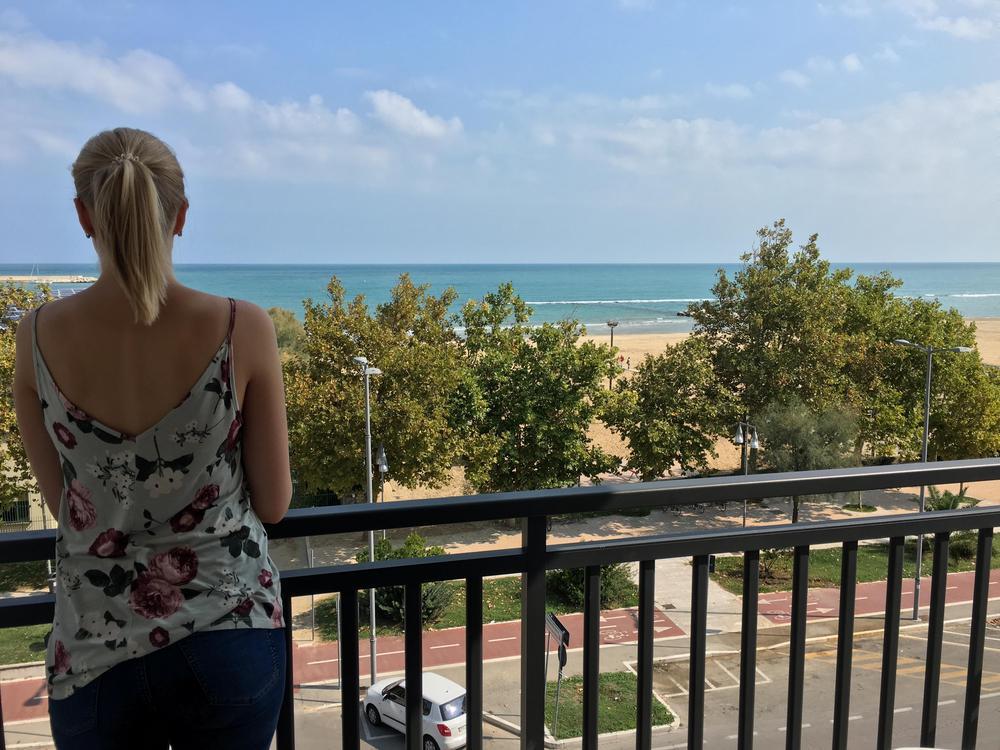 Vaaleahiuksinen nuori nainen seisoo kaiteen vieressä katsomassa merelle Italiassa.