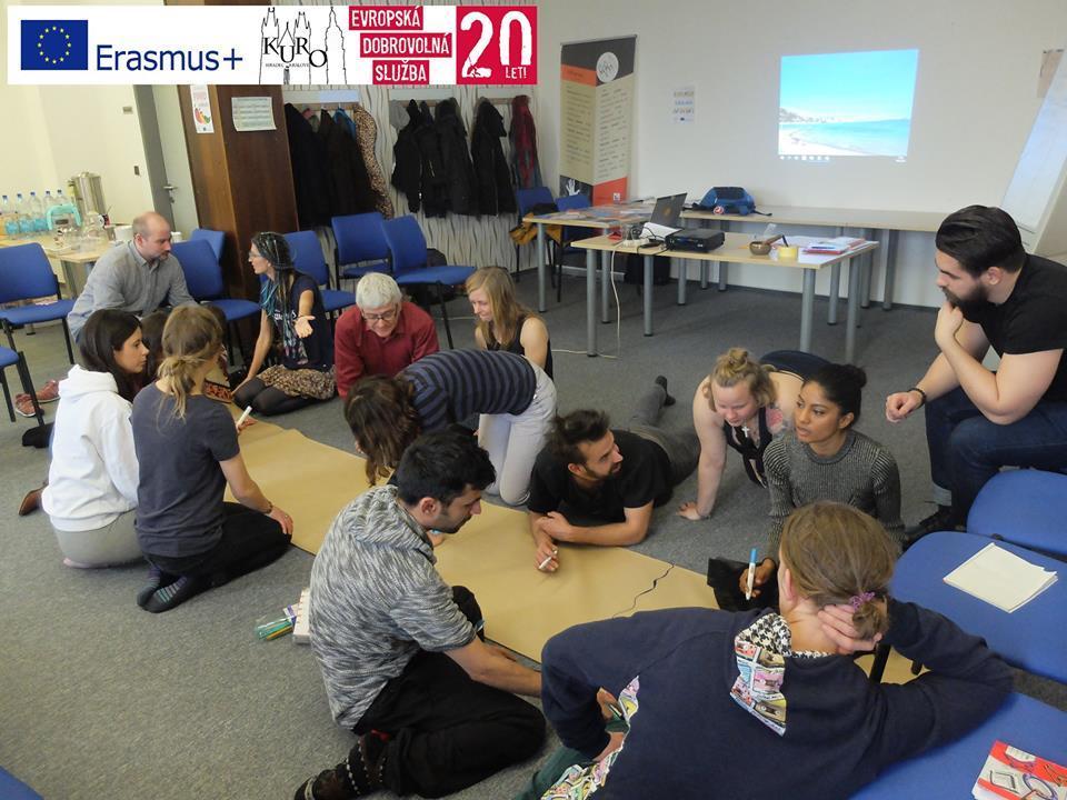 Koulutukseen osallistuvia nuoria luokkahuoneessa työskentelemässä lattialle levitetyn pitkän paperin ääressä.
