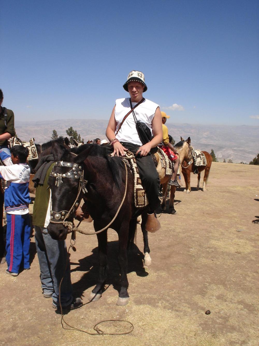 Kuvassa on jonossa ratsastajia hevosten selässä.
