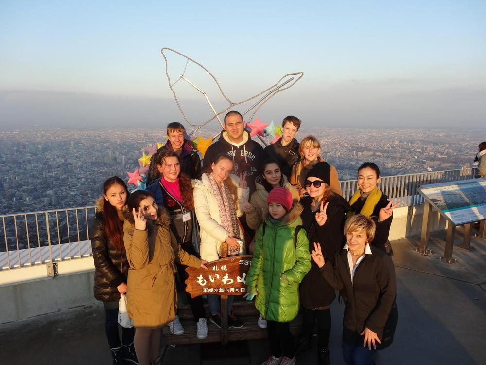 Kuva on ryhmäkuva näköalatasanteella Japanissa. Taustalla näkyy kaupunki.