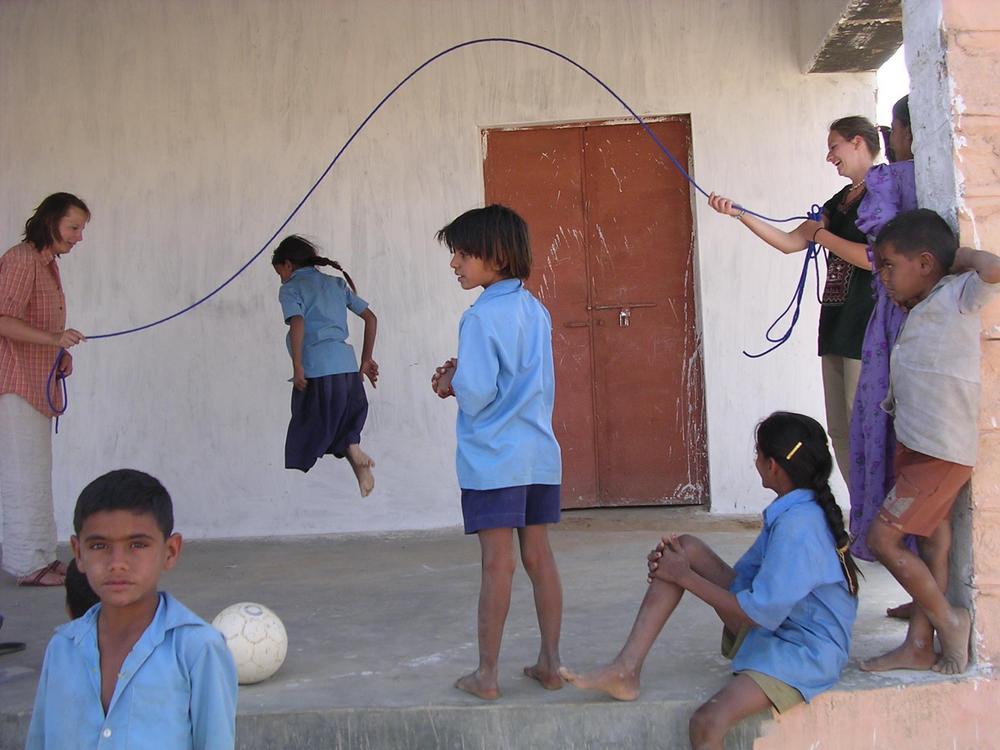 Kaksi aikuista pyörittää hyppynarua ympärillään samanlaisiin koulupukuihin pukeutuneita lapsia.