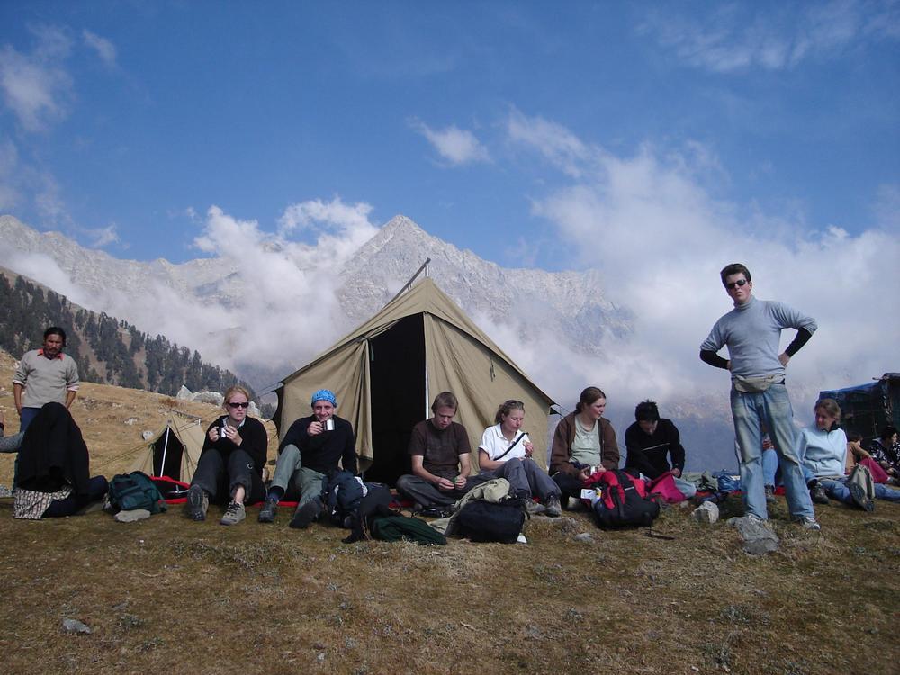Joukko aikuisia istuu leirissä taustalla lumihuippuisia vuoria.