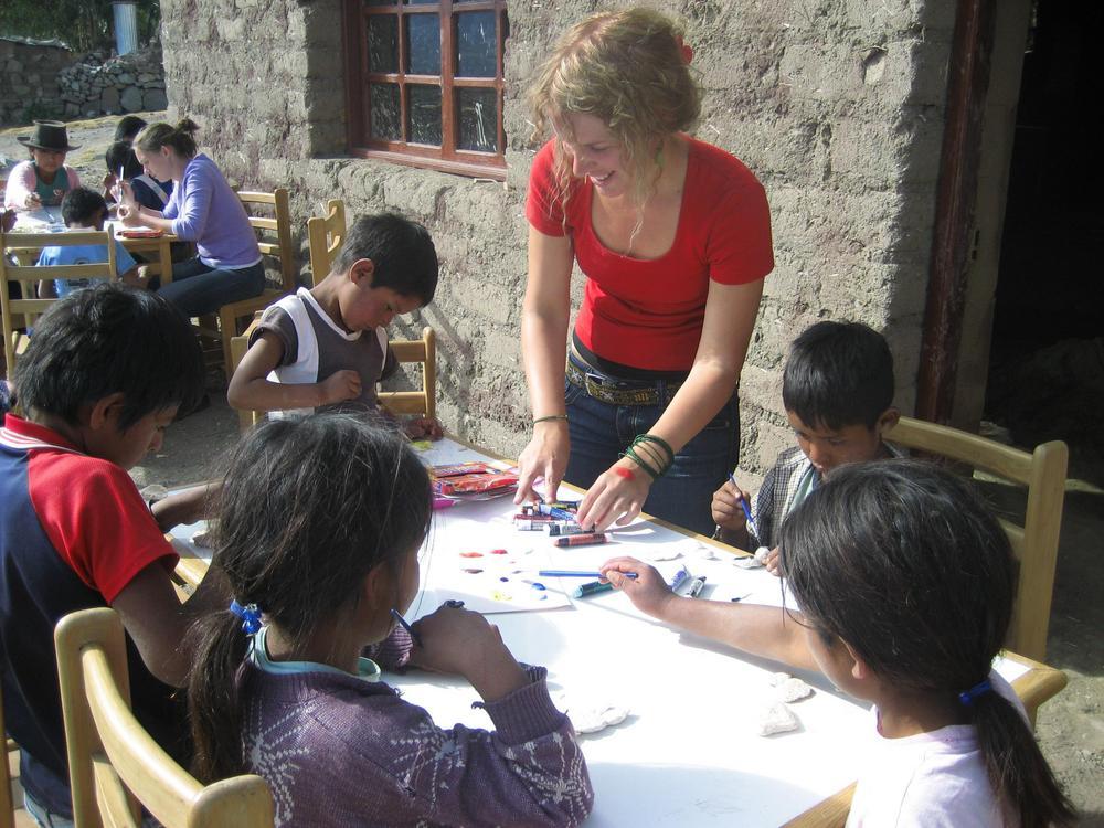 Nuori nainen ohjaamassa lasten askartelua pöydän ääressä.