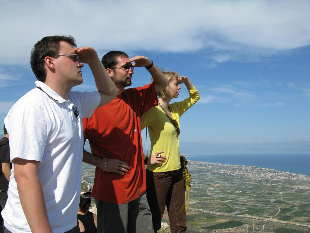 Kuvassa kolme henkilöä tähystää horisonttiin ja on nostanut käden otsalleen varjostamaan silmiä.