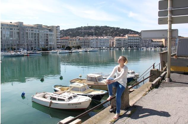 Kuvassa nainen istuu kaiteella satamassa, vieressä kolme pientä venettä.