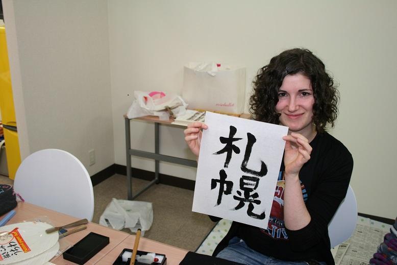Kuvassa nainen esittelee paperille maalaamiaan japanilaisia merkkejä.