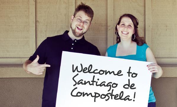 """Kuvassa mies ja nainen pitelevät kylttiä, jossa lukee """"Welcome to Santiago de Compostela"""""""