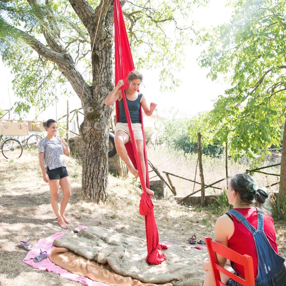 Vapaaehtoisleirillä Italiassa, nainen on punaisessa puuhun ripustetussa akrobatia kankaassa. Kaksi naista katsoo vieressä.