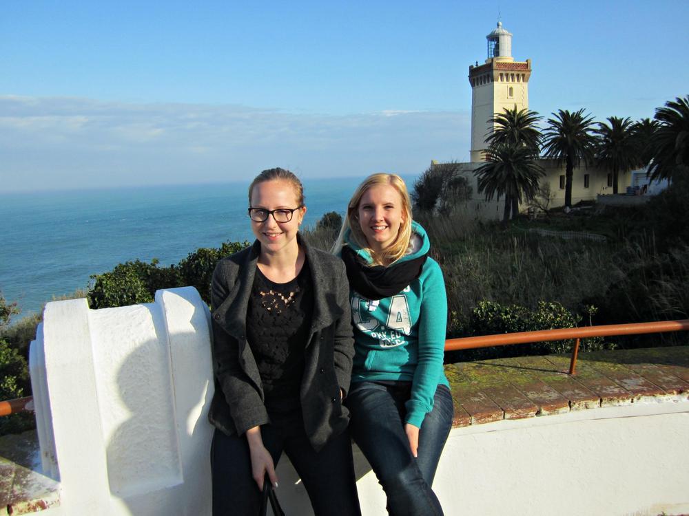 Kaksi nuorta naista istuu muurilla näköalapaikalla Espanjassa. Takana on palmuja ja meri.