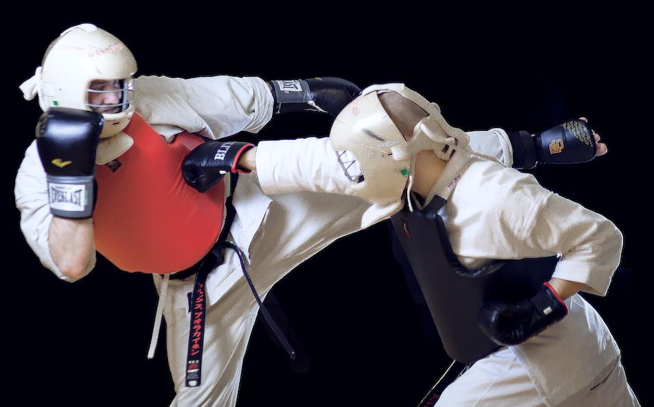 Karaten harjoittelijat ottelutilanteessa. Molemmilla on karatepuvut ja suojavarusteet yllään.