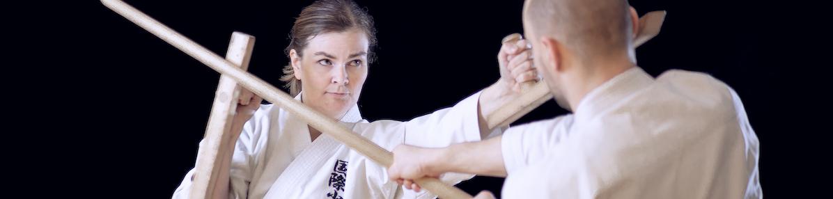 Genbu-kain karateharjoittelijoita harjoittelemassa kobudo -tekniikoita tonfilla ja bokkenilla.