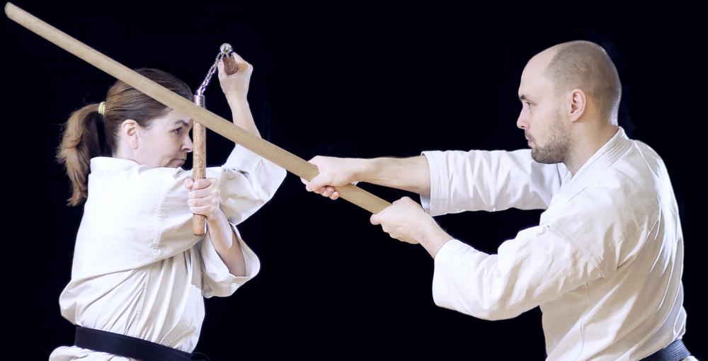 Karaten harjoittelijoita harjoittelemassa asetekniikoita nunchakulla ja bokkenilla karatepuvut yllään.
