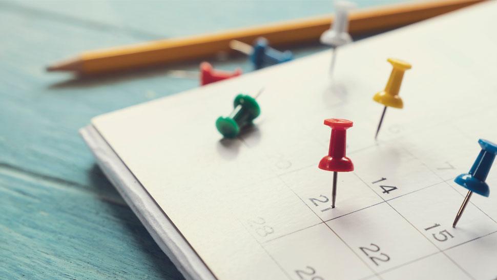 Kalenteri, jossa värikkäitä nastoja.