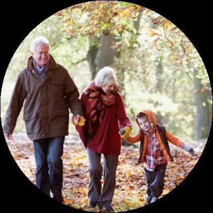 Isovanhemmat ja lapsen lapsi puistossa kävelyllä.
