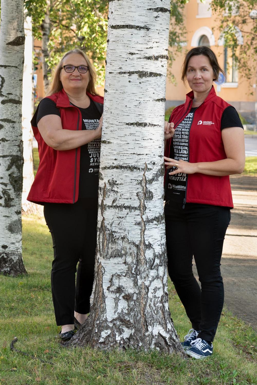 Työikäistoiminnan työntekijät Ulla Kaikkonen ja Marjut Kiviahde seisovat suuren koivun juurella.