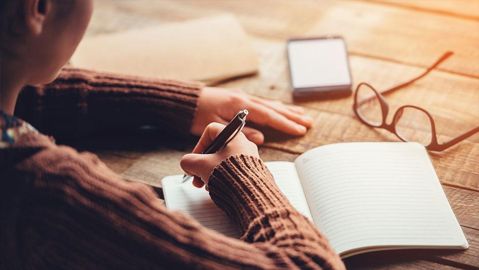 Henkilö kirjoittamassa muistioon.