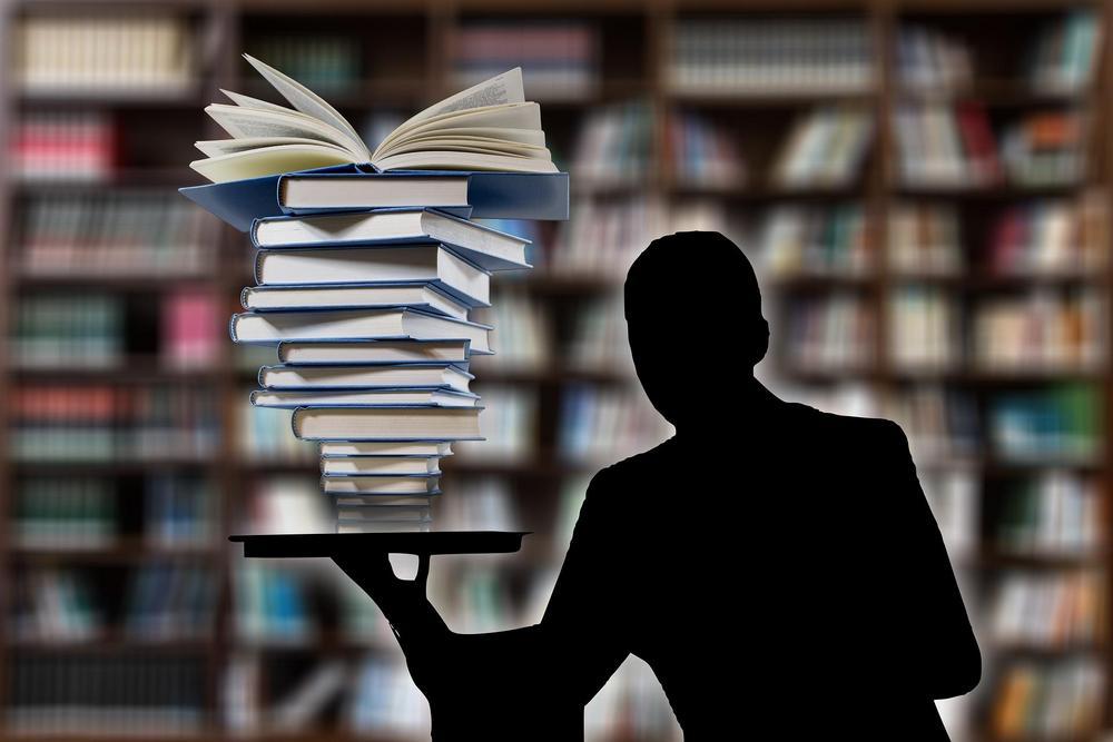 Hahmo, jolla kädessään pino tietokirjoja.