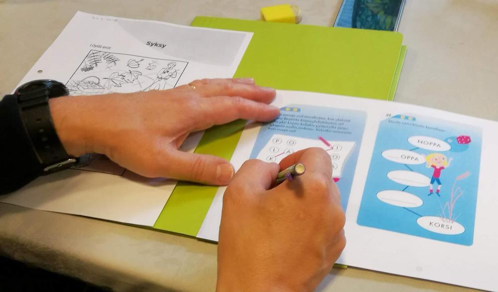 Aivotreeniryhmään osallistuja tekee kynällä päättelytehtävää.