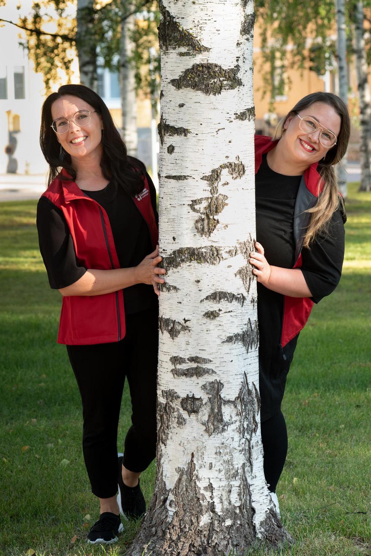 Katja ja Hanna kurkistavat puun takaa iloisesti nauraen.